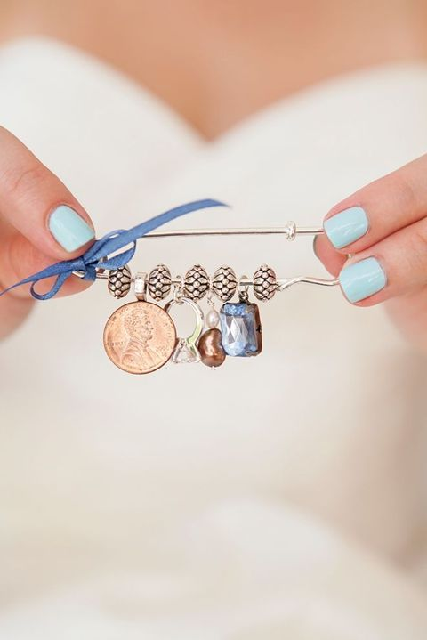 a pin with a coin, a ring, a pearl and a blue stone, a blue bow to decorate your dress