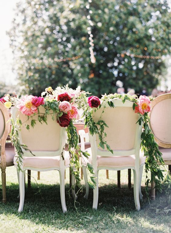 decorate your chairs with bold flowers and greenery