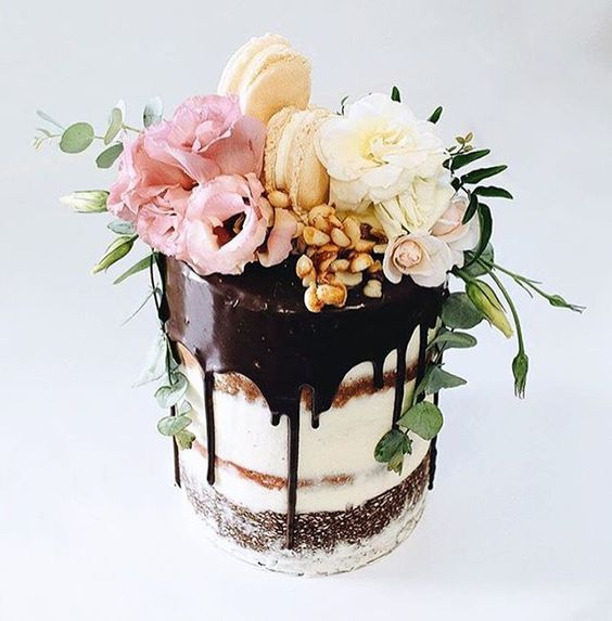 dirty frosted tall wedding cake with dark chocolate drip, macarons and ivory flowers