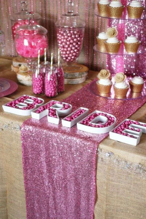 pink and gold candy table with a glitter runner