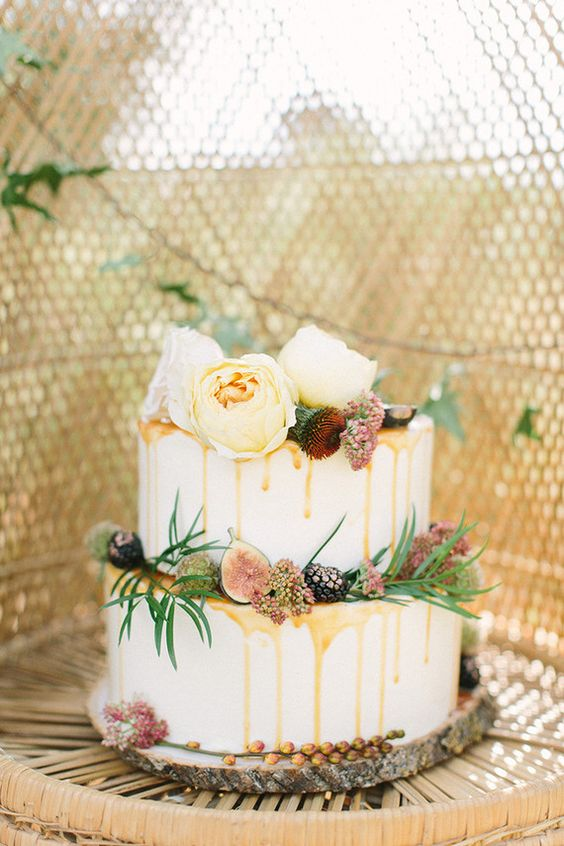 buttercup bakery wedding cake with caramel drip and topped with fruit and flowers