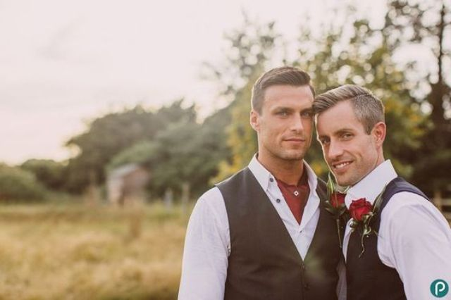 grooms wearing the same shirts and vests, red roses for boutonnieres
