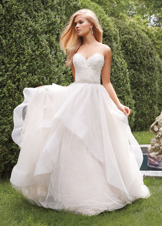 a wedding dress with a lace bodice and a dotted A line skirt