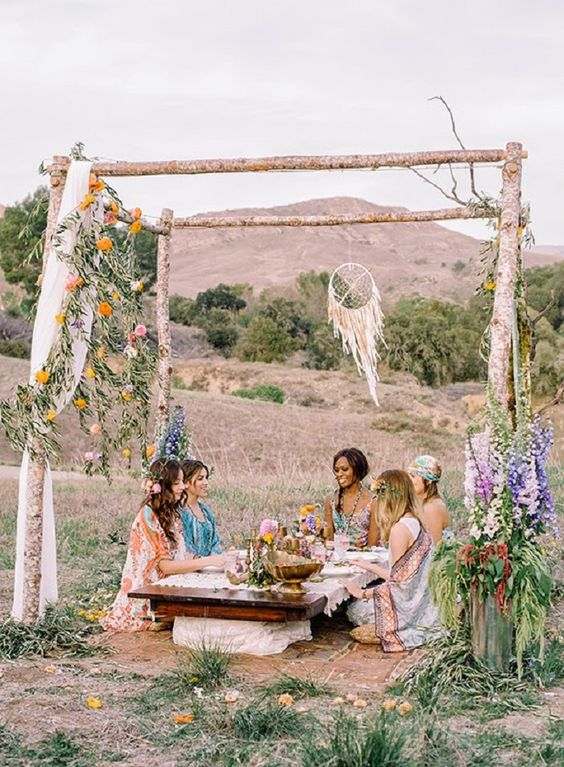 boho picnic in the middle of nature, with a rustic arch and leaves