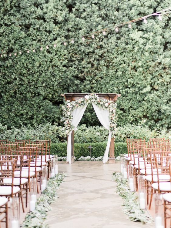 outdoor garden ceremony spot and aisle with greenery and flowers