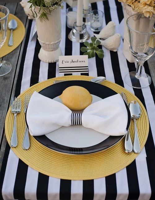 a black and white tablescape with bold yellow fabric placemats and lemons