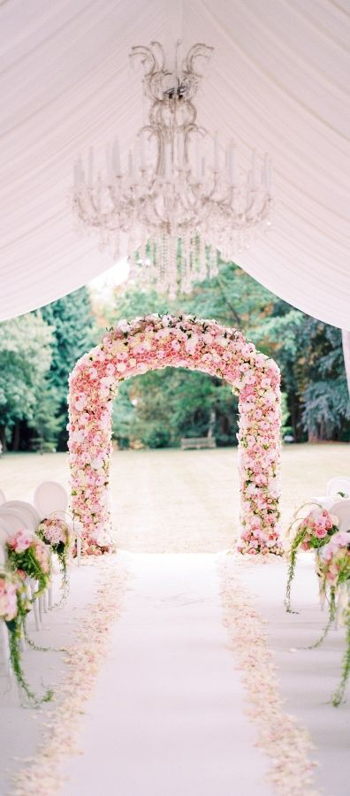 pink floral arch and aisle decor and white petals