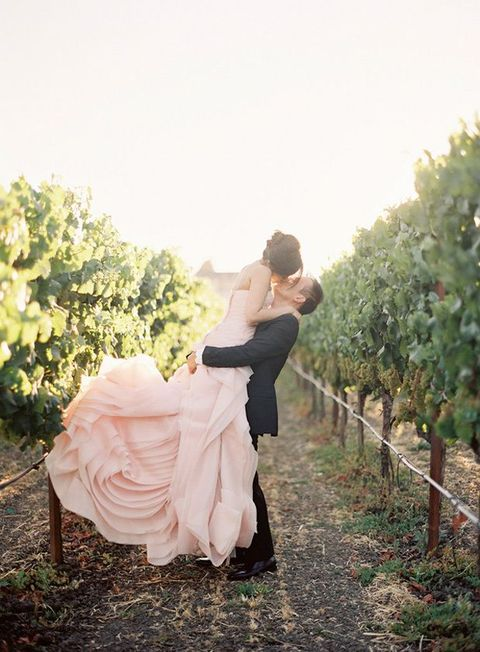 the groom in black, and the bride in blush rose-ruffle gown