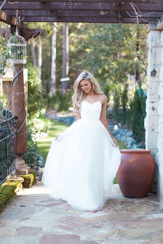 simple wedding dress with a tulle skirt and spaghetti straps for a modern bride