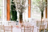 21 blush tablecloths echo with cherry blossom branches and create a stunning table setting