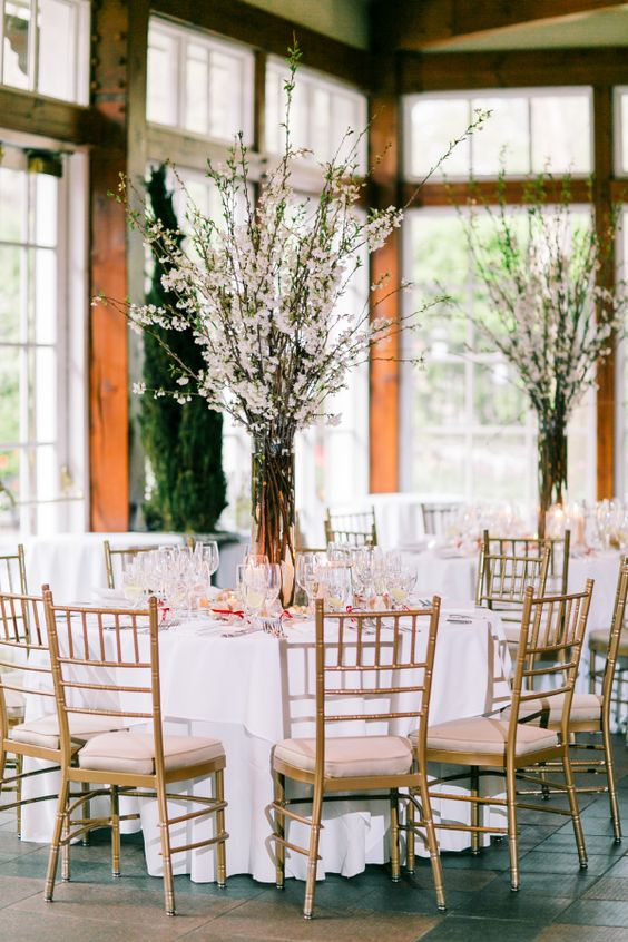 blush tablecloths echo with cherry blossom branches and create a stunning table setting