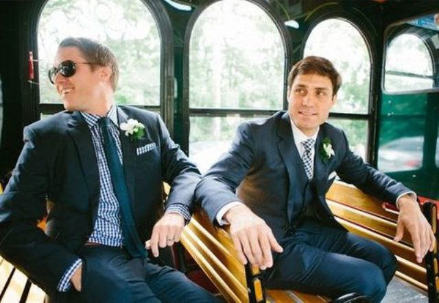 same navy suits, a shirt that matches the other groom's tie