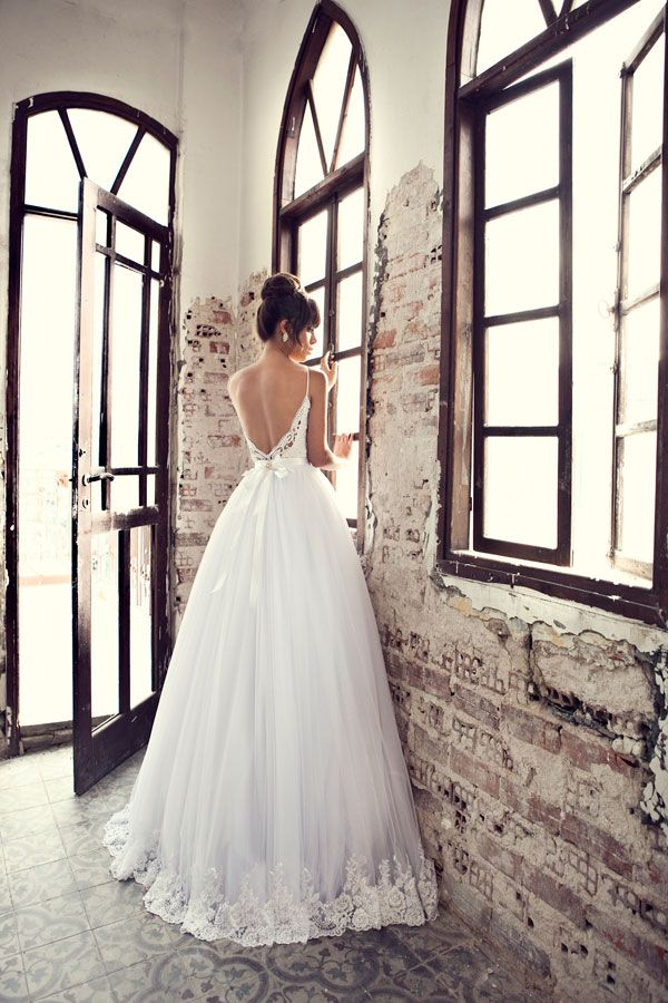 a spaghetti strap dress with an open back, a bow on the back and lace decor on the tulle skirt