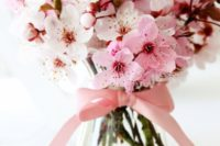 22 cherry blooms in a glass vase with a pink bow on it