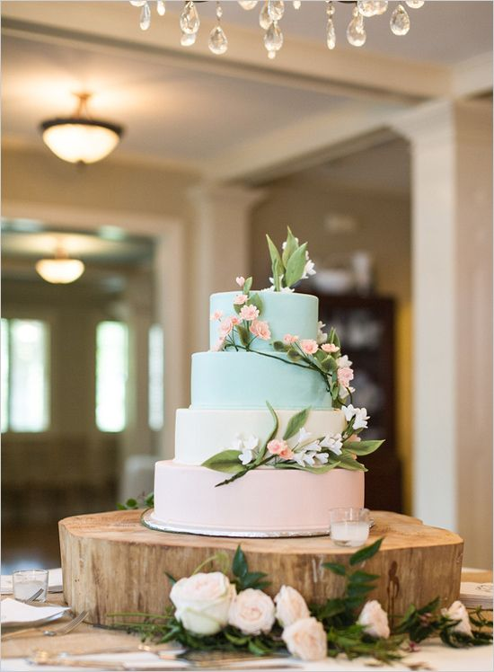 a wedding cake with two peach and two mint layers topped with flowers