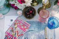 23 mismatched bold and bright napkins and indigo tie-died placemats for a boho table