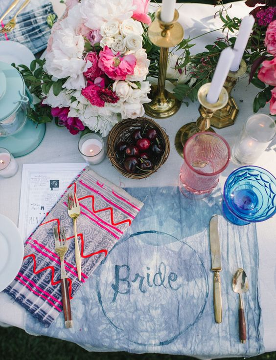 mismatched bold and bright napkins and indigo tie-died placemats for a boho table