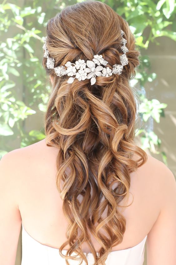 curled half updo with a headpiece