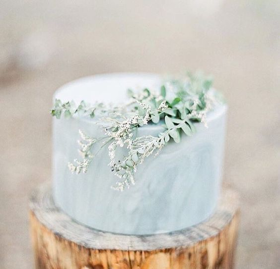slate blue one-tier marble cake topped with fresh greenery