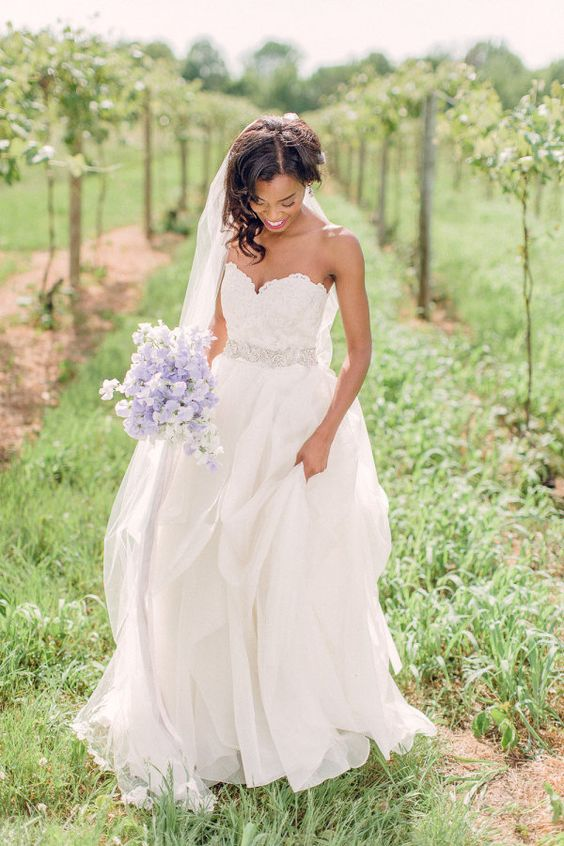 sweetheart wedding dress with a flowing skirt and an embellished sash