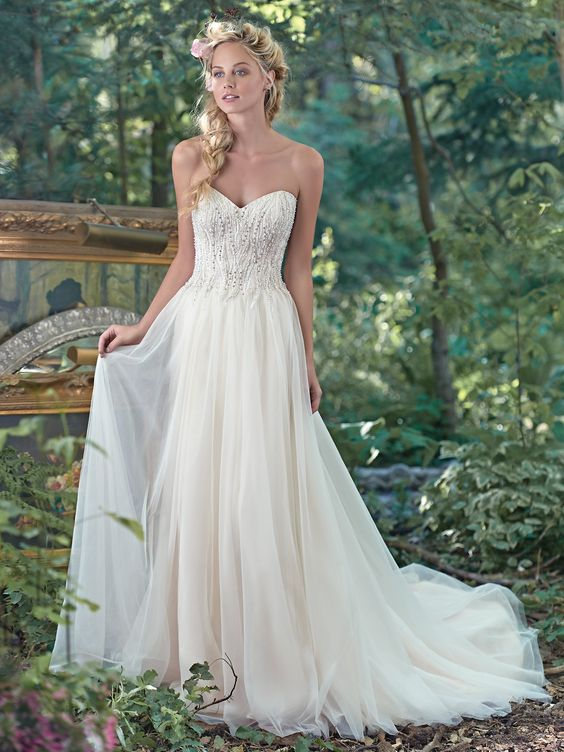 Swarovski crystals, glamorous pearls, and shimmering sequins on the bodice and a flowing skirt