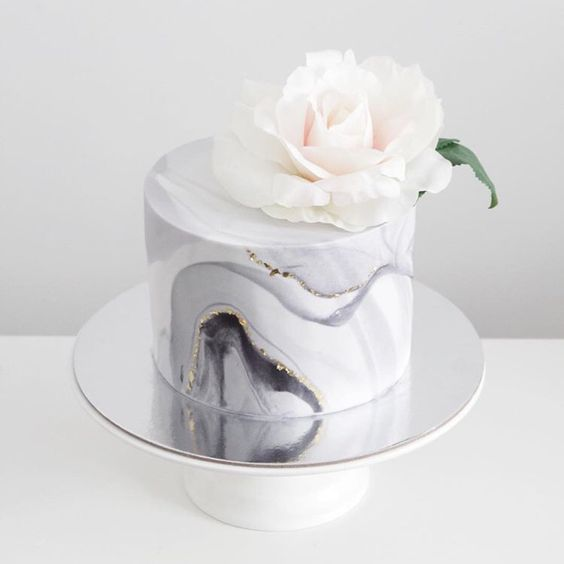 marble grey one-tier wedding cake with a sparkel topped with a large bloom