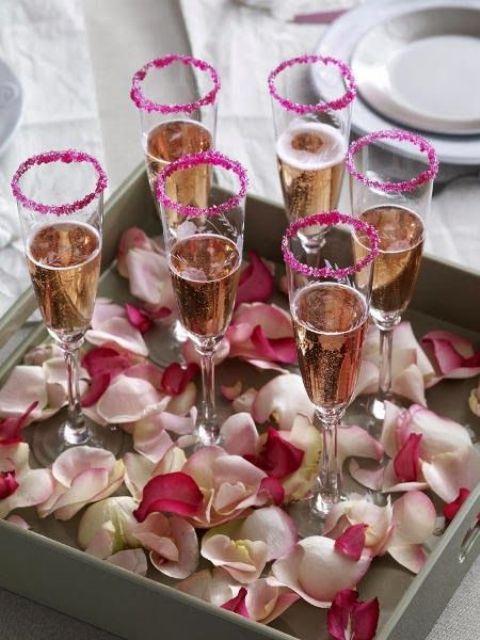 pink glitter rim champagne flutes and rose petals