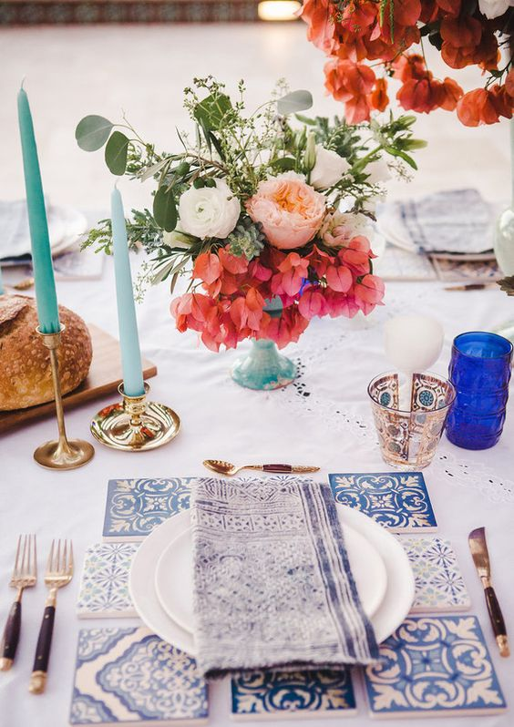 a Mediterrnean table setting with an azulejo tile placemat, blue candles and colored florals