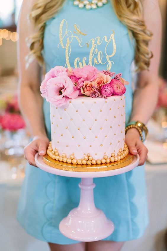 blush and gold cake topped with bold pink flowers