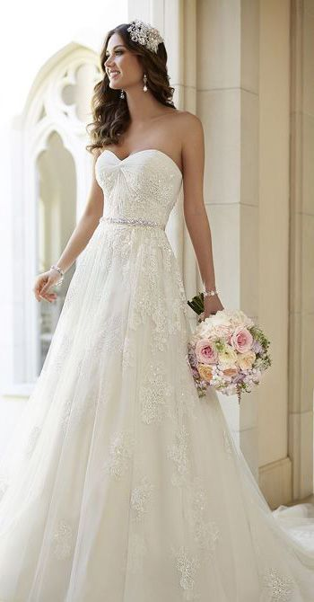 lace wedding gown with an embellished sash and a train