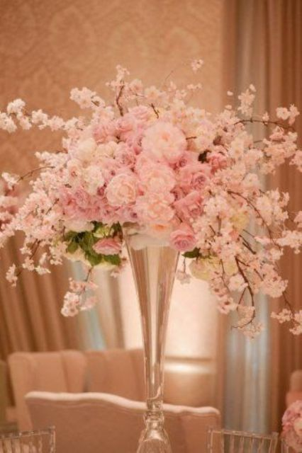 lush cherry blossom and roses centerpiece in a glass vase