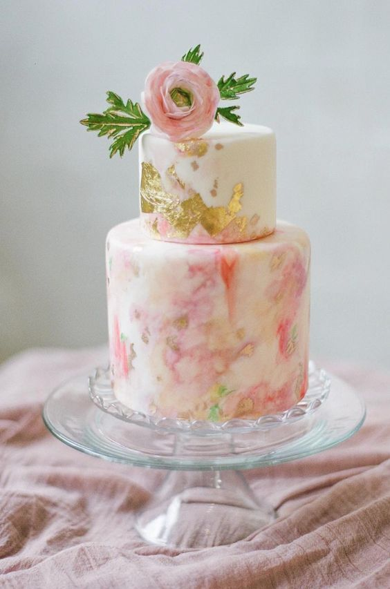 peach marble wedding cake  with gold leafing and topped with peach flowers