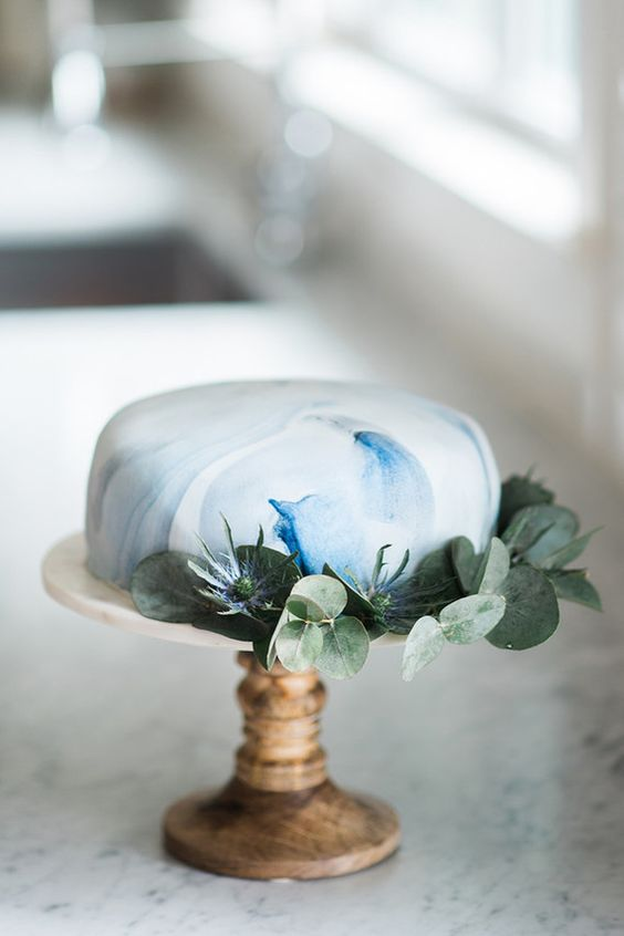 marbled blue one-tier cake decorated with greenery and thistles