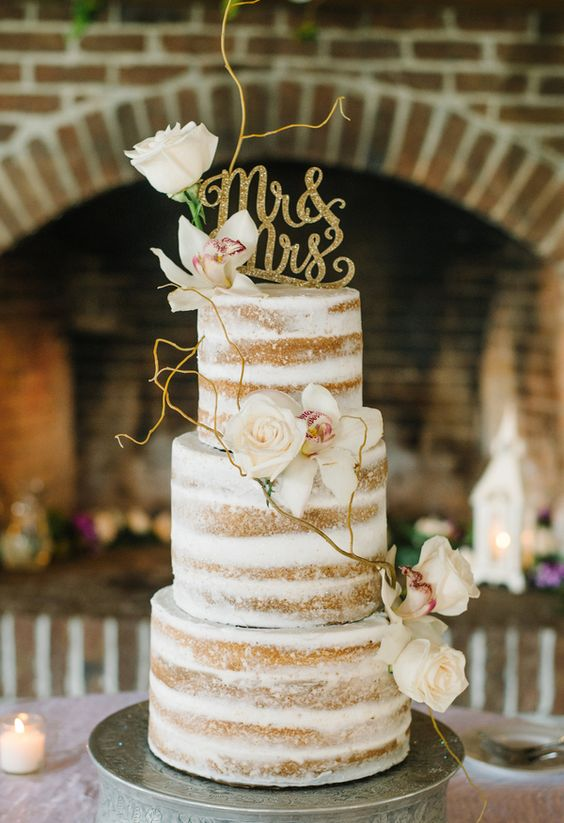 dirty frosted wedding cake decorated with flowers, branches and glitter toppers