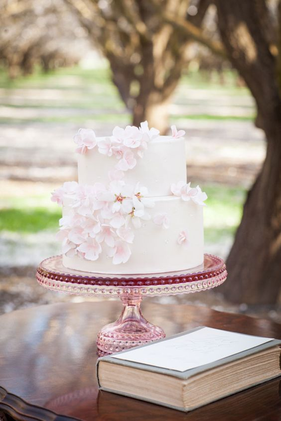 a blush wedding cake decorated with blossoms