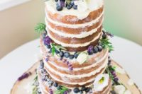 33 a naked cake topped with blueberry, lavender and white flowers