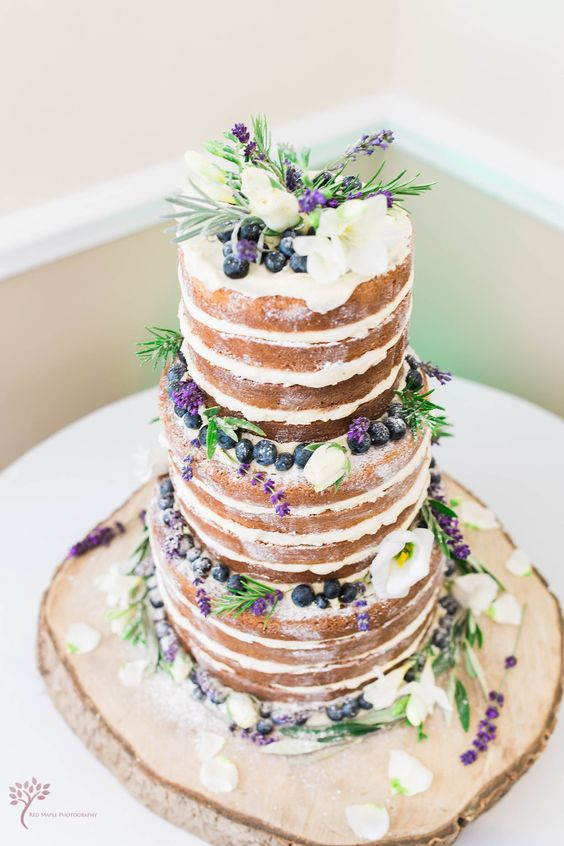 a naked cake topped with blueberry, lavender and white flowers