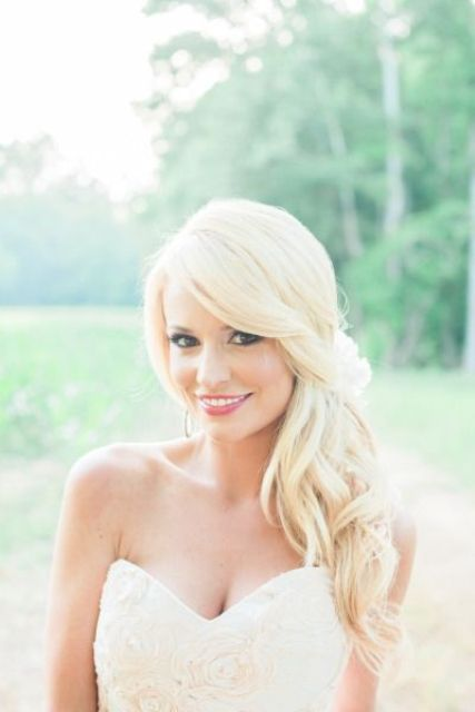 side swept wavy hairstyle looks very romantic and glam