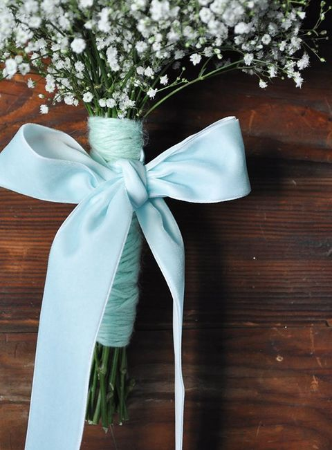 a tiffany blue yarn bouquet wrap and a ribbon bow look heavenly with baby