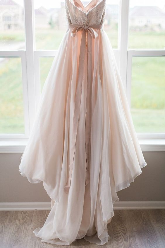 blush lace wedding dress with a flowy skirt and a bow