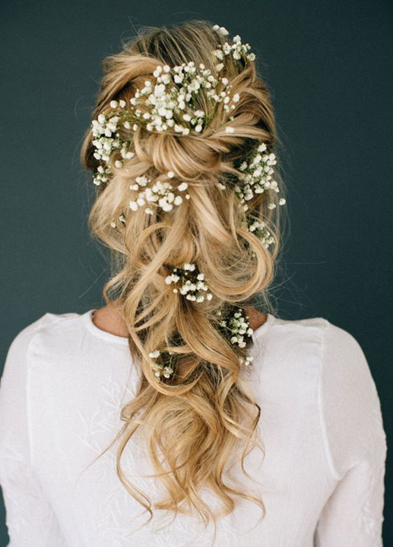 large curls pinned with baby's breath tucked into it