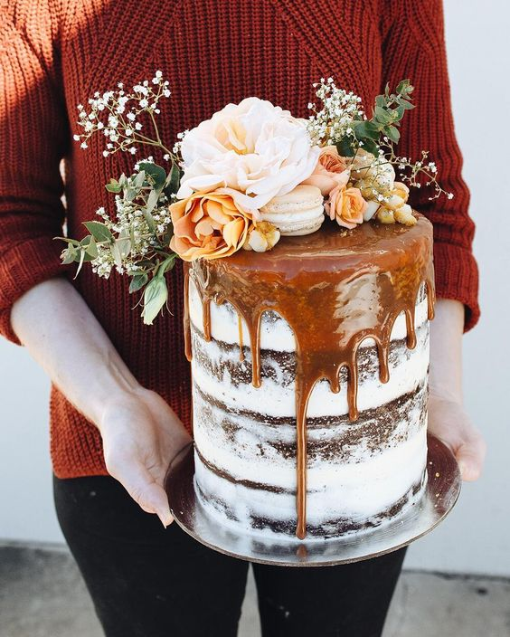 salted caramel drip layer cake with a fresh flower and macaron topper