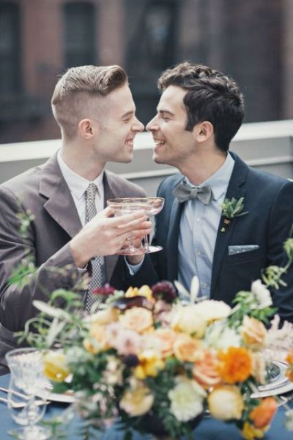a brown suit with a tie, a dark grey suit with a bow tie to express the personality of each groom