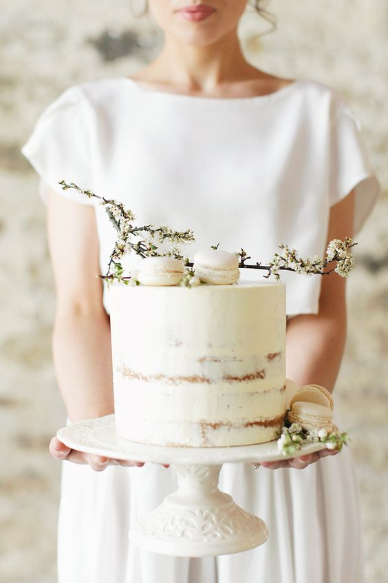 beautiful dirty frosted wedding cake with ivory macarons and flowers