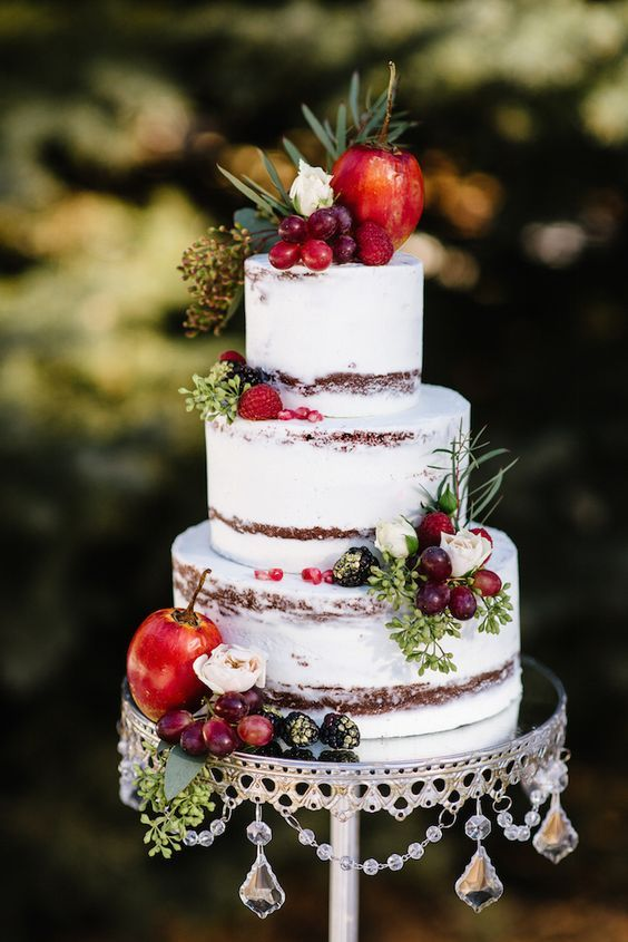dirty frosted wedding cake topped with berries and fruits