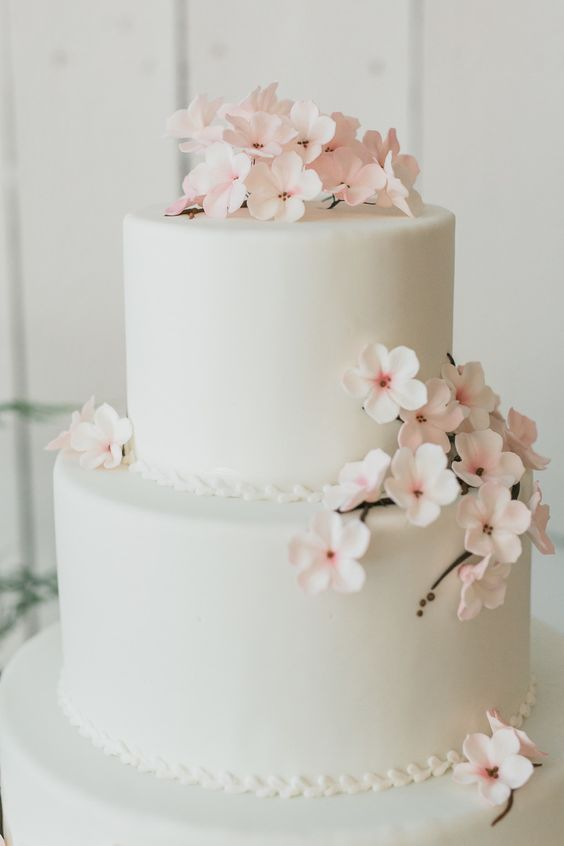ivory wwedding cake topped with cherry flowers