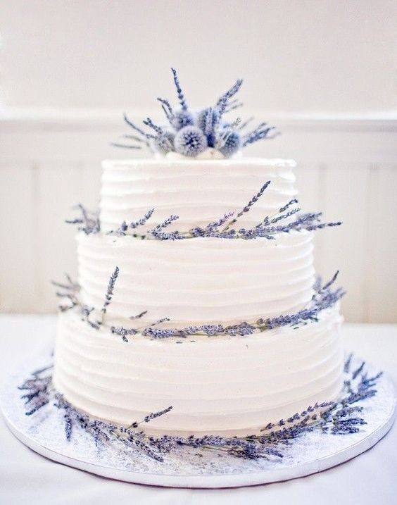 three-tier wedding cake topped with lavender and thistle