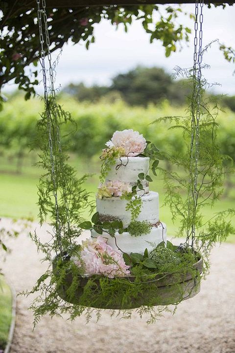 semi naked wedding cake with blush flowers and a lot of greenery on a hanging display