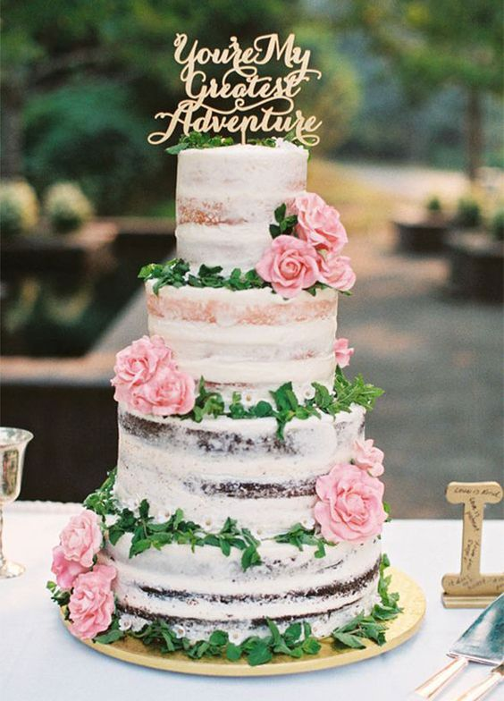 semi naked wedding cake with pink roses and a calligraphy topper