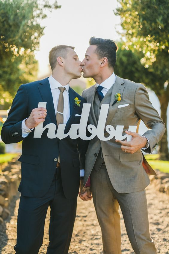 stylish grooms in beige and navy, the ties match each other's suits